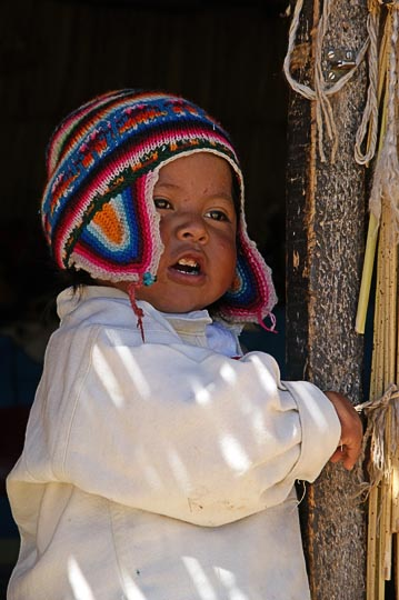 A cute little Aymara boy with a warm and colorful knitted hat, at the entrance of his Totora reeds hut, Islands of Uros, Lake Titicaca 2008
