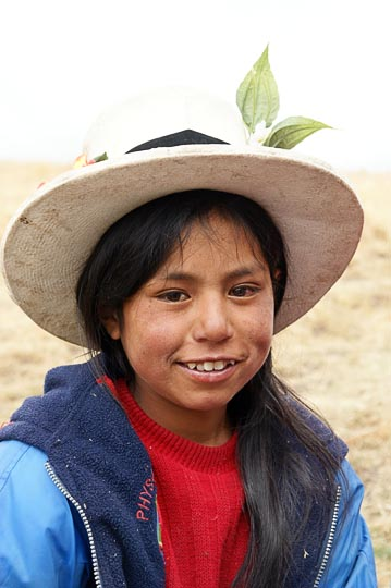 A young student with a with a flower-strewn hat at a school picnic, Hatun Machay, Cordillera Negra 2008