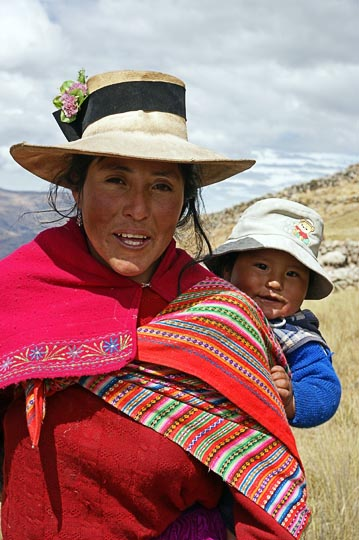 A Chola (local woman) carrying her baby close to their nomadic hut, Hatun Machay, Cordillera Negra 2008