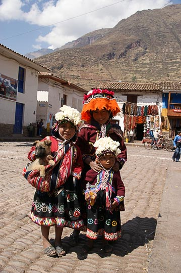 Three girls in traditional colorful clothes in the central plaza, Pisac 2008