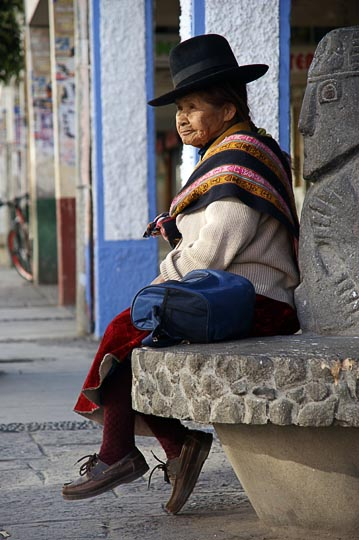 A Chola (local woman) sitting on a bench on main street, Huaraz 2008