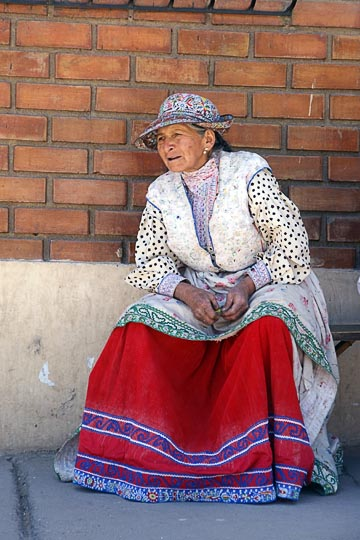 A Chola (local woman) sitting on a bench on main street, Cabanaconde 2008