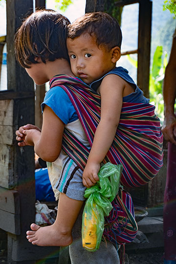 A girl carrying her younger brother on her back, central Bhutan 2018