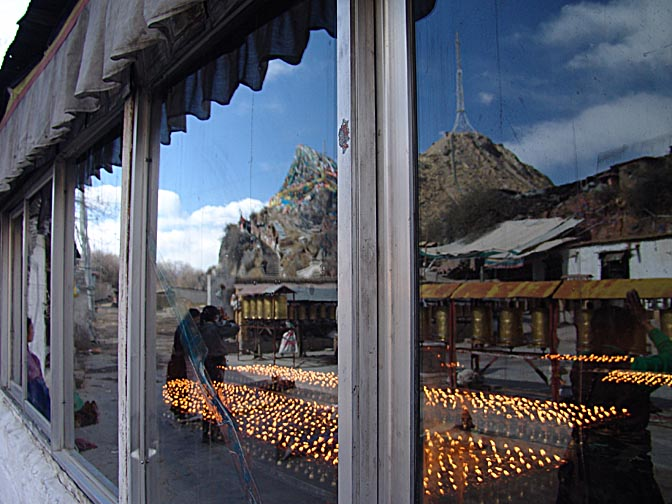 Butter candles, prayer wheels and the Chakpori reflection in the window, Lhasa 2004