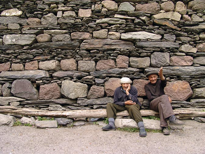 Two locals sitting on a log in Kazbegi, South Ossetia 2007