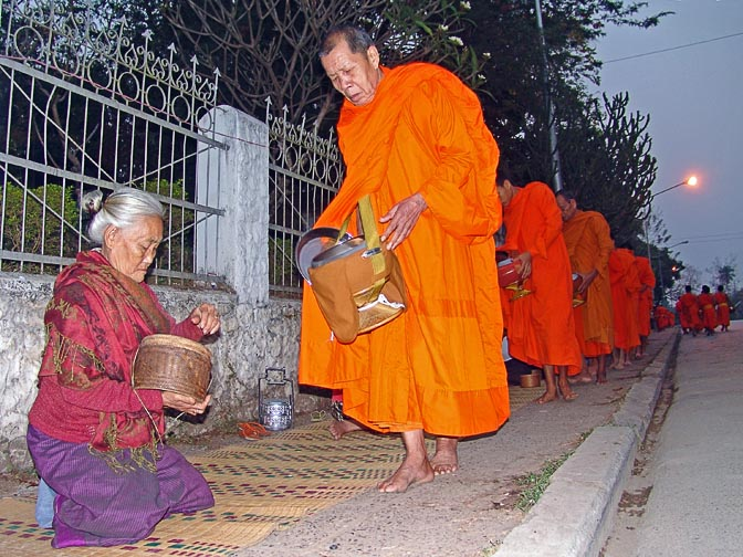 Local women giving alms to the monks very early in the morning, in a Buddhist regimented ritual of 'making merit', Luang Prabang 2007