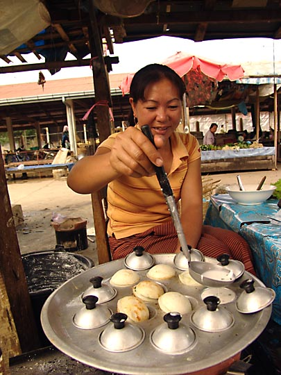 A local woman preparing pancakes in the morning market, Vang Vieng 2007