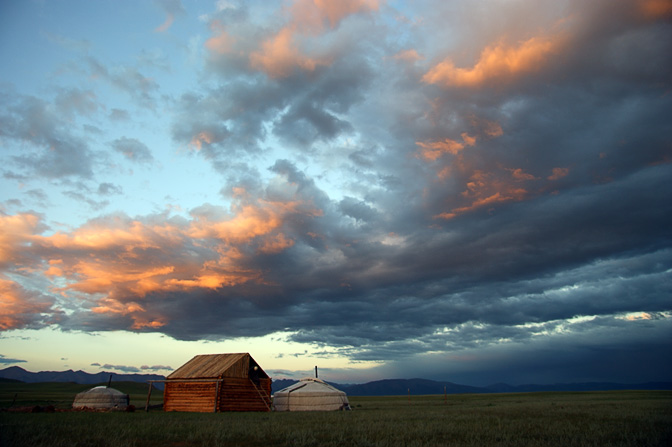 Family Gers (Mongolian home tent) and a wooden hut near Renchinlkhumbe at sunset, North Mongolia 2010