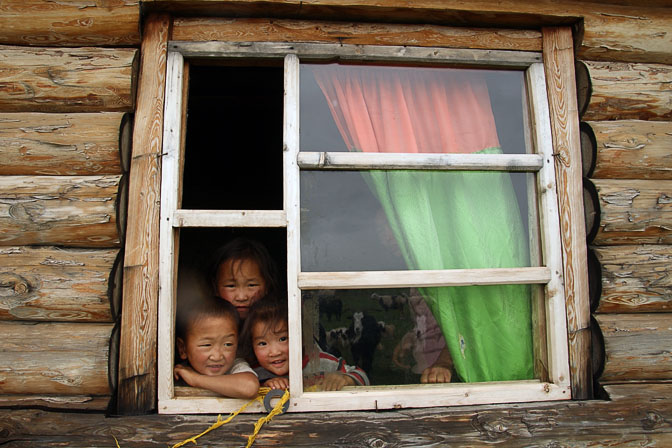 Smiling children in a window of a family wooden hut near Renchinlkhumbe, North Mongolia 2010