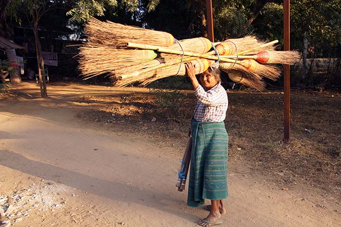 A woman carrying brooms on her head, Bagan 2015