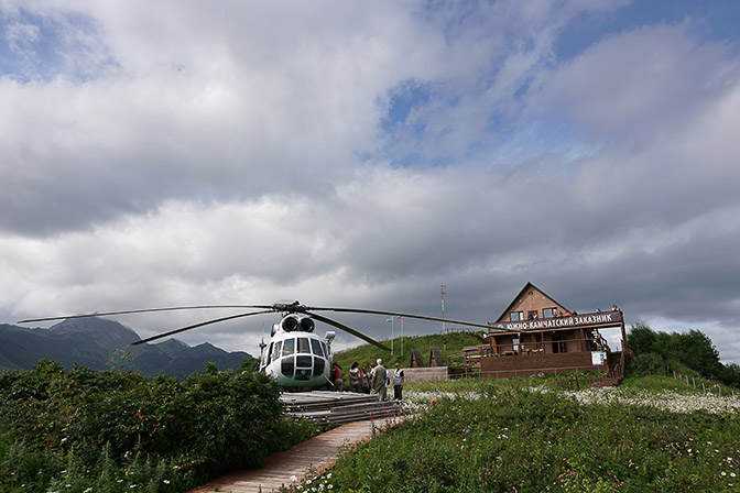 A helicopter and the wooden lodge at Grassy Point, Kuril Lake 2016