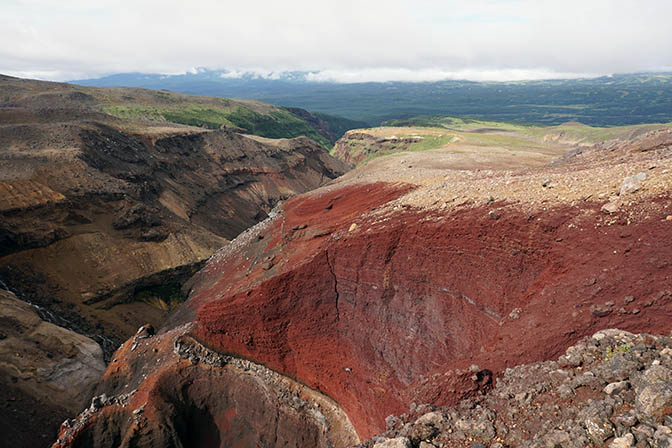 Red lava walls at the deep canyon created by the river that drains the caldera of Mutnovsky Volcano, 2016