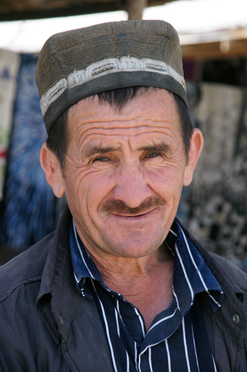 Tajik man wearing a traditional hat in the market, Khushikat 2013