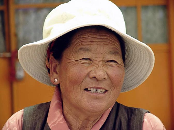 A smiling Tibetan woman at The Dalai Lama birthday ceremony, in the Temple at McLeod Ganj, Dharamsala, India 2004