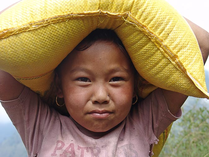 A Nepali girl carrying rice on her head, on the way from Kenja to Sete, along the Khumbu Trail to the Everest, Nepal 2004