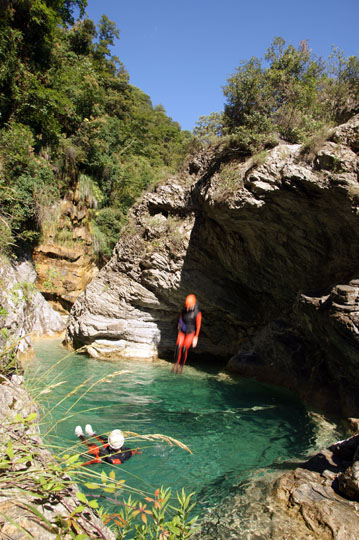 Dudi jumps down a rock-ledge into a clear pool in the Barbaira Canyon, Italy 2011