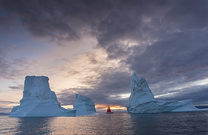 A yacht with red sails cruising between icebergs at dusk, 2017