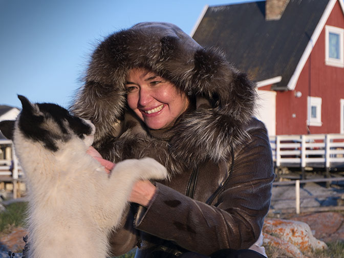Paarna, an Inuit woman, frolicking with a puppy in Ilimanaq, 2017