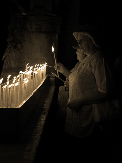 Lighting candles by the Greek Orthodox altar at Calvary, or Golgotha, inside the church of the Holy Sepulchre, The Old City 2010 (Sepia tone)