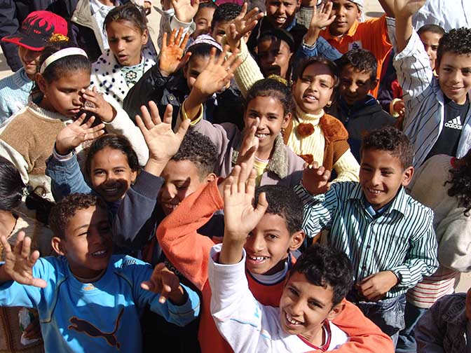 School kids waving for welcome while visiting The Mortuary Temple of Ramesses III at Medinet Habu, 2006