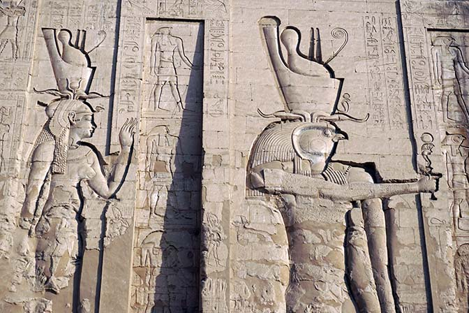 The huge bas-reliefs of god Horus, falcon headed, and his wife goddess Hathor, decorate the north wall of the Temple at Edfu, 2017