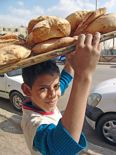 A young boy carries Pita bread from the bakery in Giza, Cairo 2006