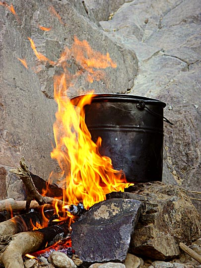 Cooking in a sooty pot on open fire in Wadi Feid, 2003