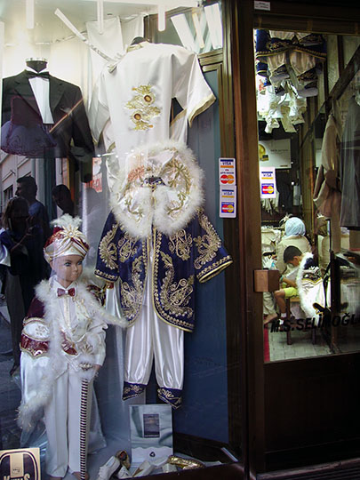 A reticent kid inside a circumcision outfit store, 2003