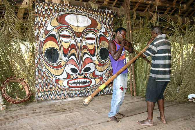Yugin and friend play the bamboo flute inside a Haus Tambaran (Spirit House) in Kanganaman, the Sepik River 2009