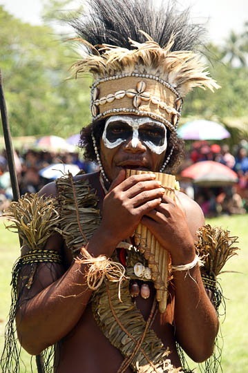 A young man from the West New Britain Province, playing a bamboo flute at The Wewak Garamut and Mambu Festival 2009