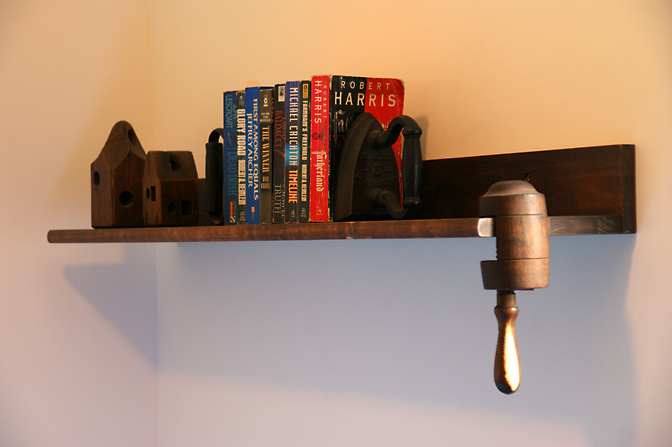 A bookshelf in Jack's bedroom, with old irons that support the books and special wooden items, 2009