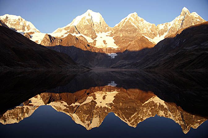 The sunrise red colors on the three peaks of The Great Mount Yerupaja reflected in Lake Carhuacocha, 2008