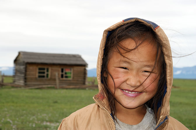 A smiling girl by her wooden hut near Renchinlkhumbe, North Mongolia 2010