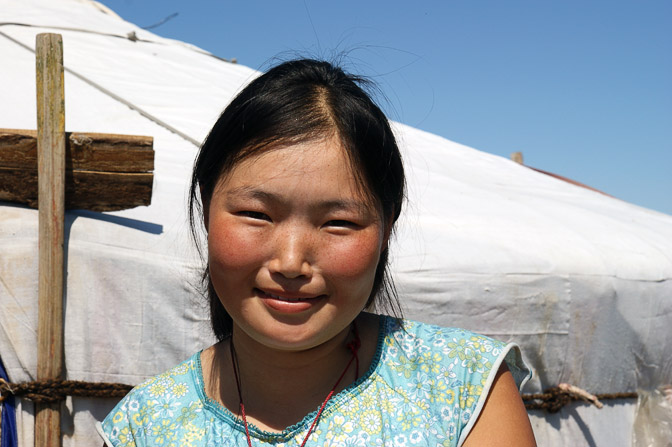 A smiling young girl by her family Ger (Mongolian home tent) close to Darkhan, Central Mongolia 2010