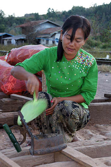 A woman lighting the coals in a charcoal iron in the train station, Kalaw to Inle Lake trek 2015