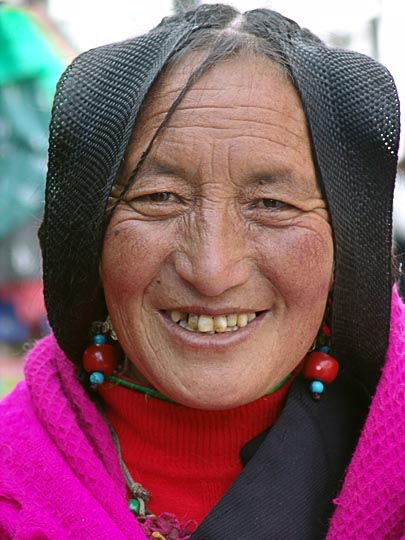 A Tibetan woman with woven hair, on pilgrimage along the Lingkor around the Jokhang, Lhasa, Tibet, China 2004