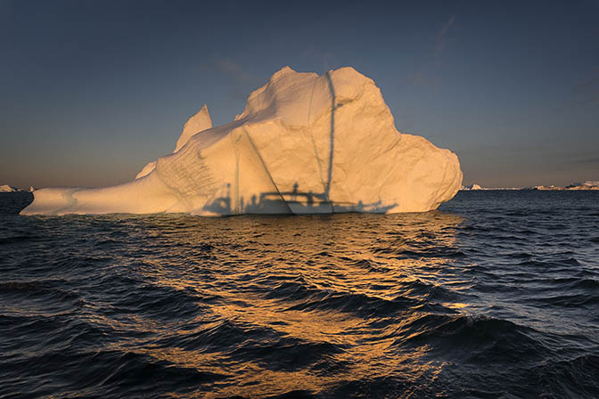The first rays illuminate the iceberg in golden light, with the silhouette of the yacht from which it was shot, 2017
