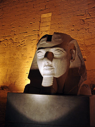 A statue of Ramesses II in front of the entrance Pylon to the Luxor Temple of Thebes, illuminated at night, 2006