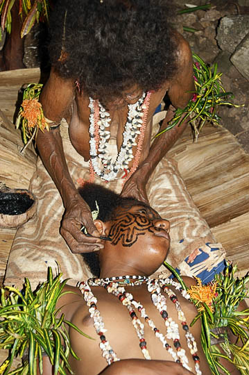 An artist demonstrates the process of tattooing a face of a young adolescent, Komoa Village 2009